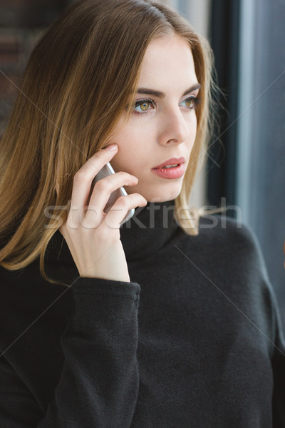 Attractive serene young lady talking on mobile phone Stock photo © deandrobot
