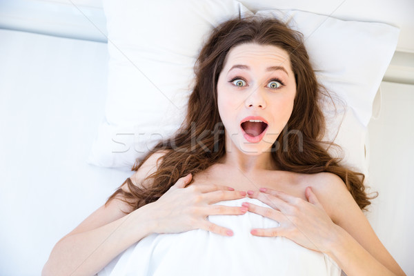Amazed beautiful young woman wake up in bed Stock photo © deandrobot