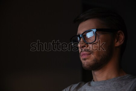 Serious man in glasses using headphones and looking at screen Stock photo © deandrobot