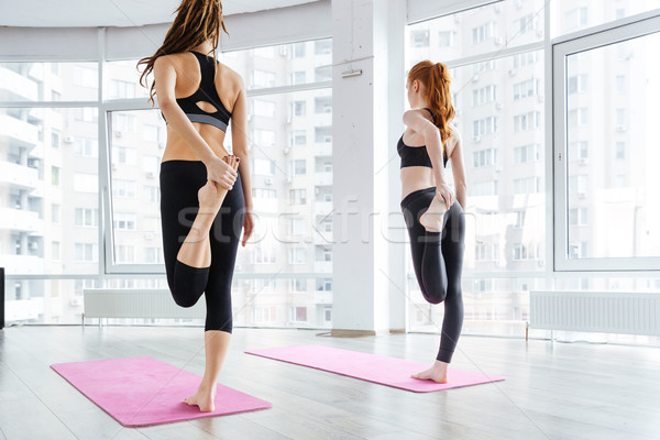 Two women standing and stretching legs on pink yoga mat Stock photo © deandrobot