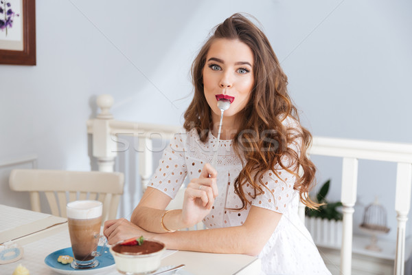 Funny woman sitting at cafe with spoon in her mouth  Stock photo © deandrobot