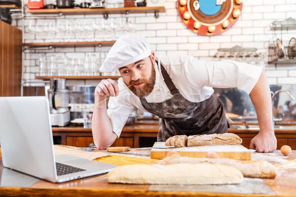 Baker pane utilizzando il computer portatile cucina Foto d'archivio © deandrobot