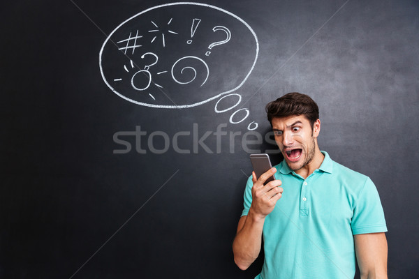 Mad furious young man using smartphone and shouting Stock photo © deandrobot
