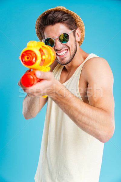 Cheerful young man having fun using water gun Stock photo © deandrobot