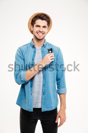 Smiling attractive young man in hat standing and holding sunglasses Stock photo © deandrobot
