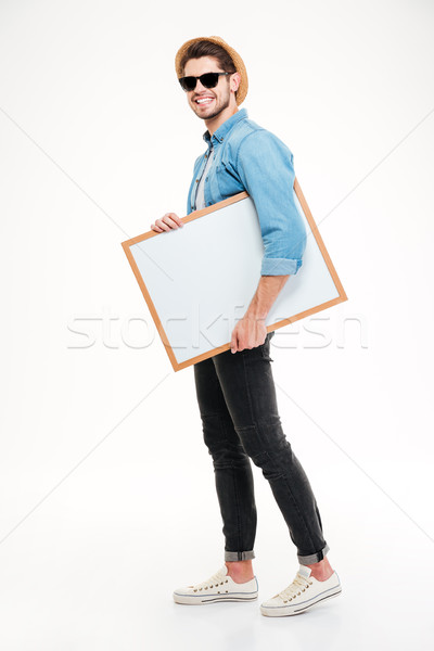Happy smiling young man walking and holding blank whiteboard Stock photo © deandrobot