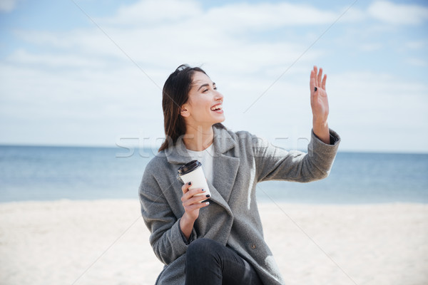Cheerful pretty attractive woman waving to someoone at the seaside Stock photo © deandrobot