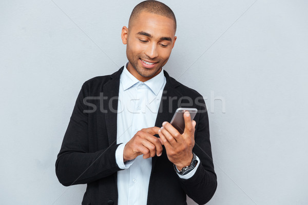 Man looking at his smart phone while text messaging Stock photo © deandrobot