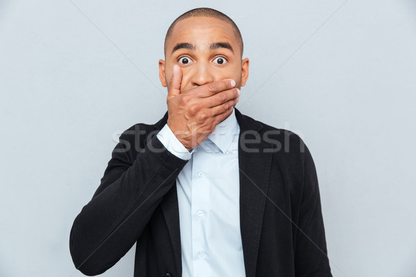 Handsome african man covering mouth with hand isolated on gray Stock photo © deandrobot