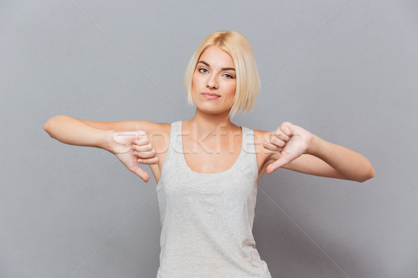 Sad unhappy young woman showing thumbs down with both hands Stock photo © deandrobot