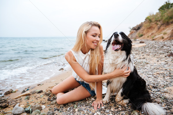 Cheerful woman sitting with her dog on the beach Stock photo © deandrobot