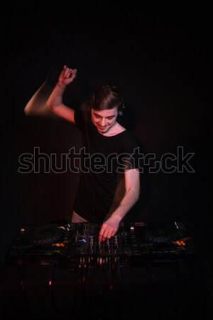 Dj using turntables and mixing tracks Stock photo © deandrobot