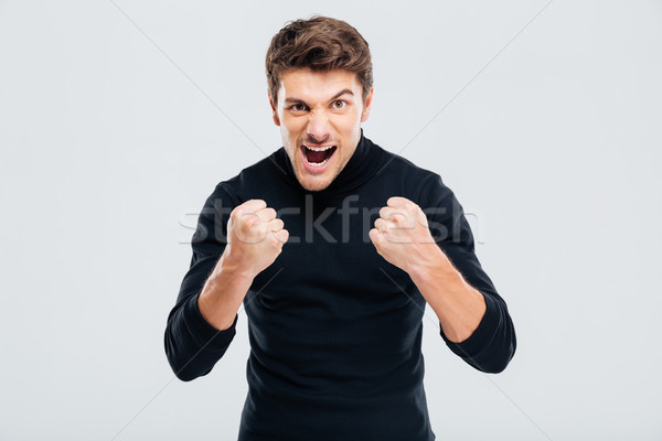 Mad crazy young man threatening with fists and shouting Stock photo © deandrobot
