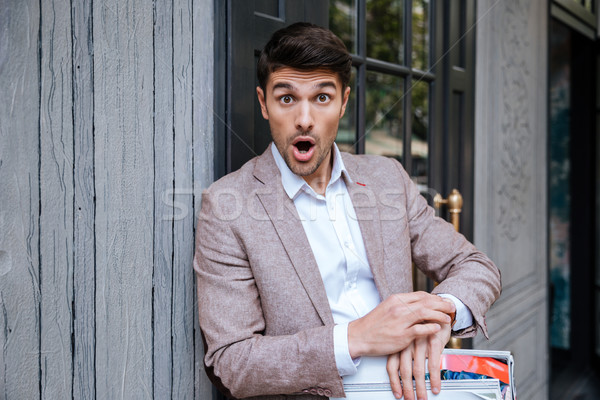 Close-up portrait of surprised man looking at watch outdoors Stock photo © deandrobot