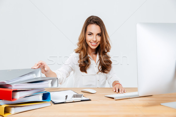 Smiling cheerful businesswoman sitting at her working place Stock photo © deandrobot