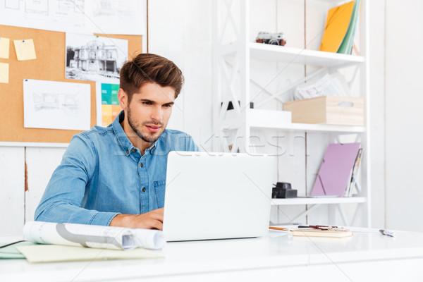 Pensieroso giovani casuale imprenditore utilizzando il computer portatile ufficio Foto d'archivio © deandrobot