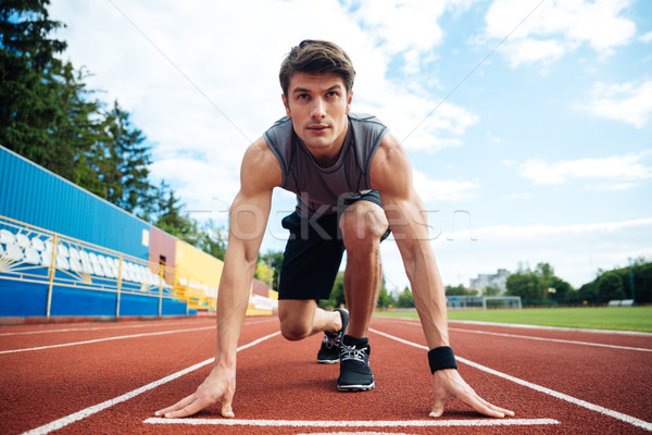 Young man in starting position for running on sports track Stock photo © deandrobot