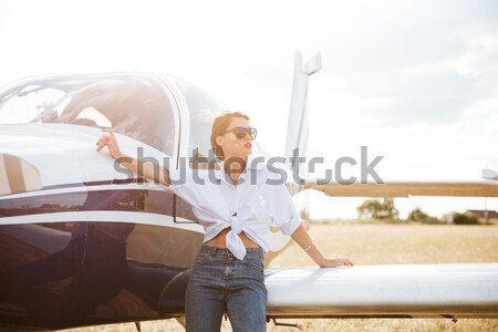 Beautiful woman in sunglasses posing near a plane Stock photo © deandrobot