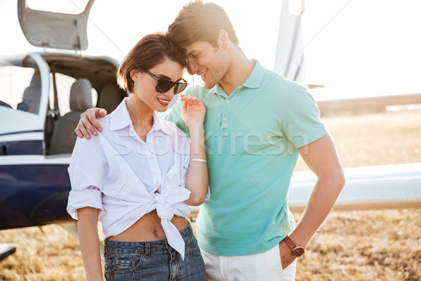 Stock photo: Couple standing and hugging near small airplane