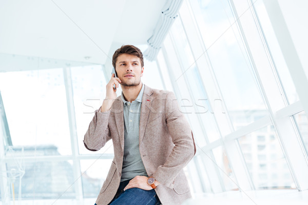 Attractive young businessman talking on mobile phone while sitting Stock photo © deandrobot