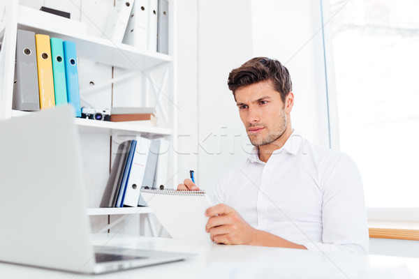 Closeup of young businessman sitting and writing in notepad Stock photo © deandrobot