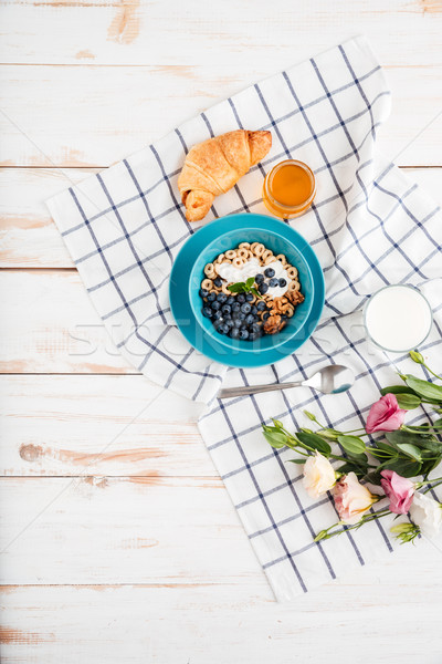 Oat cereals with berries and cream, cup of milk, flowers Stock photo © deandrobot