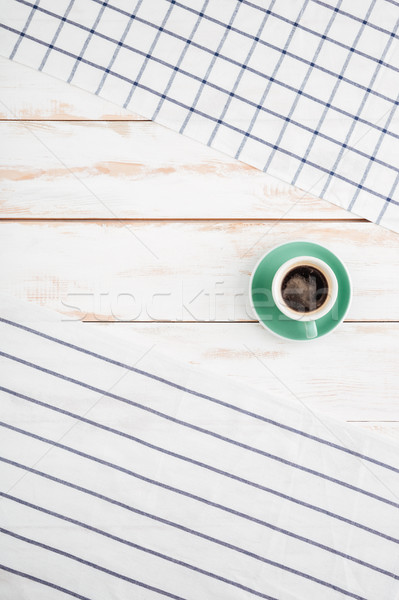 Cup of coffee between striped and plaid napkins Stock photo © deandrobot