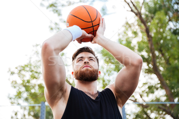Portrait of a handsome man in sports wear playing basketball Stock photo © deandrobot