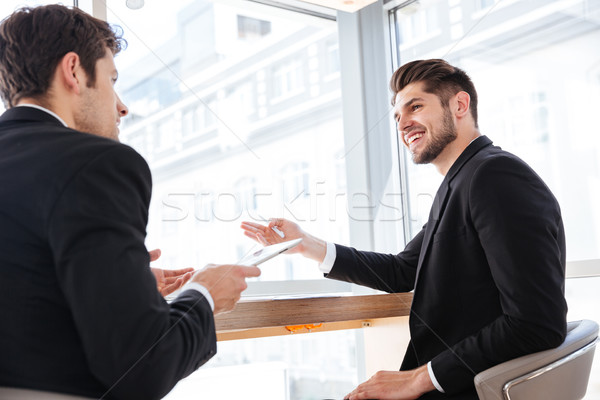 Two cheerful young businessmen using tablet on business meeting Stock photo © deandrobot