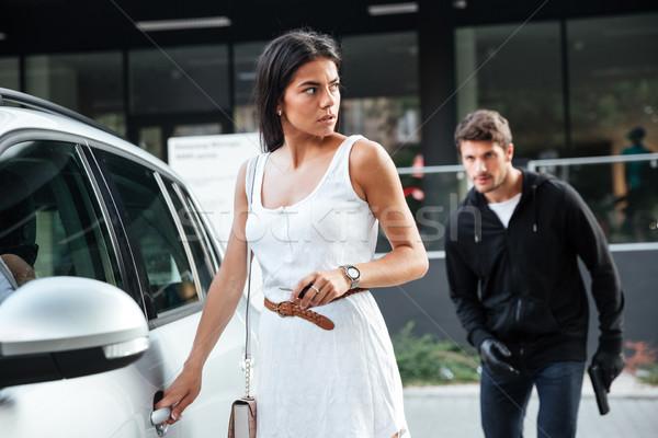 Homem ladrão mulher jovem abertura carro perigoso Foto stock © deandrobot