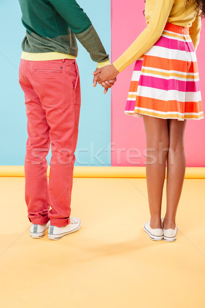 Legs of couple standing and holding hands Stock photo © deandrobot