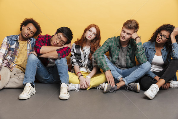 Group of tired young people sitting and sleeping Stock photo © deandrobot