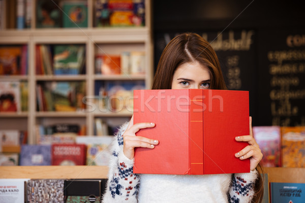 Portrait of a brunette woman covering her face with book Stock photo © deandrobot
