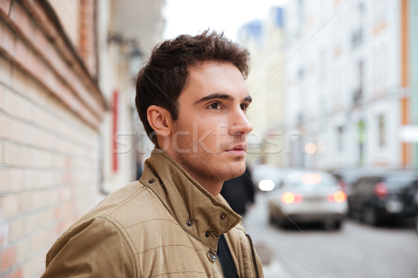 Concentrated young man walking on the street Stock photo © deandrobot