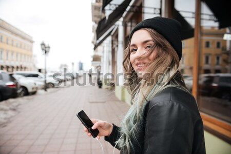Cheerful man walking on the street and talking by phone. Stock photo © deandrobot