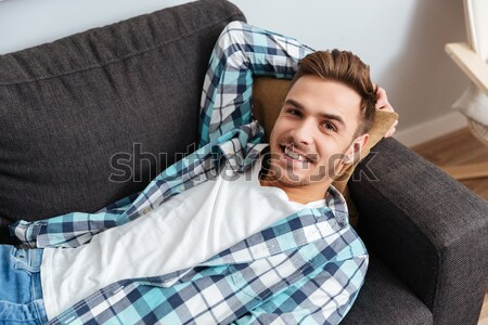 Tired young man lies on sofa at home and sleeping Stock photo © deandrobot