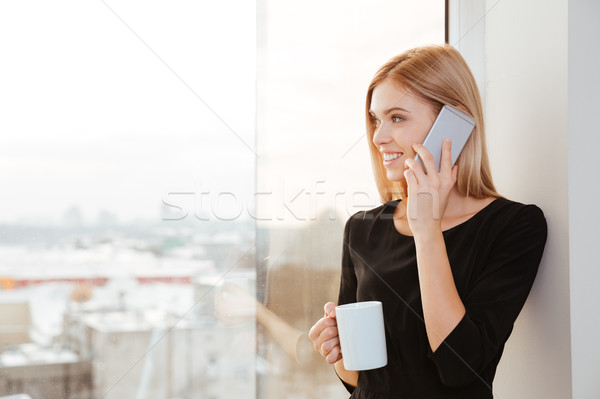 Smiling young lady worker holding coffee while talking by phone Stock photo © deandrobot