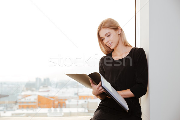 Smiling young lady worker in office holding folder. Stock photo © deandrobot
