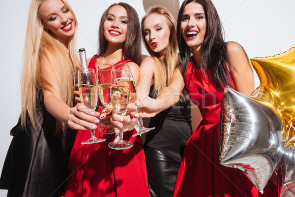 Joyful women clinking glasses and drinking champagne on the party Stock photo © deandrobot