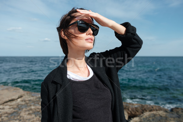 Woman in sunglasses standing and looking far away on seashore Stock photo © deandrobot