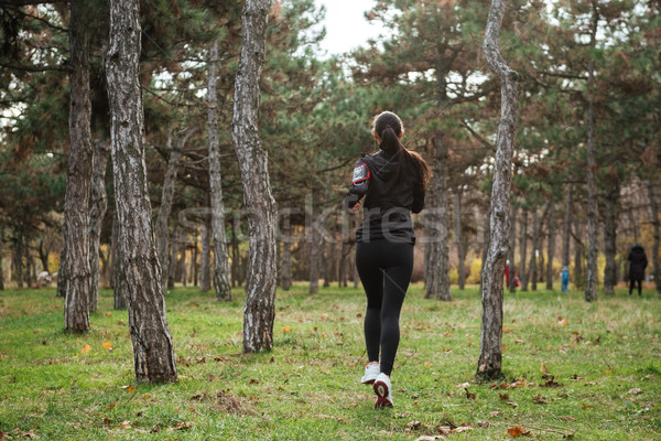 Back view of young woman runner in warm clothes Stock photo © deandrobot