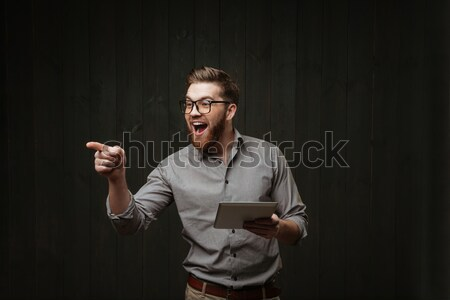 Man looking up while holding open book and cup Stock photo © deandrobot