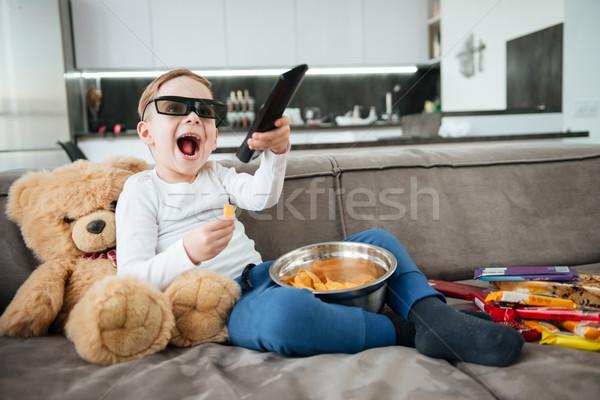 Happy boy on sofa with teddy bear watching TV Stock photo © deandrobot