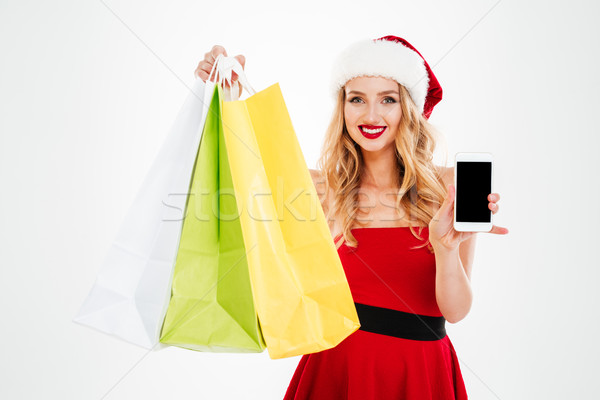 Woman in santa claus costume with shopping bags showing smartphone Stock photo © deandrobot