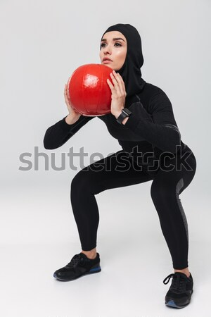 Full length of woman athlete working out with red ball Stock photo © deandrobot