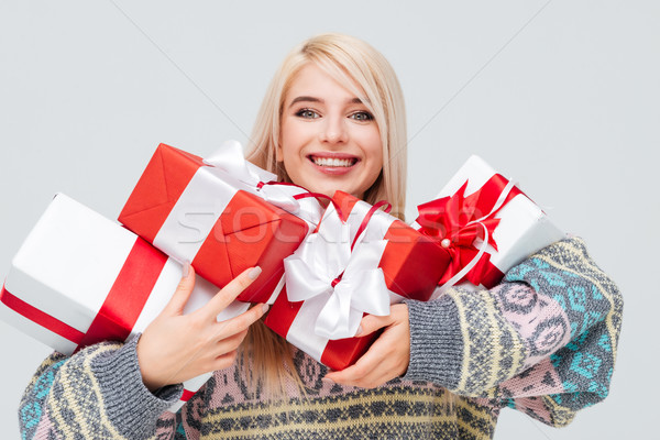 Woman holding heap of gift boxes and looking at camera Stock photo © deandrobot