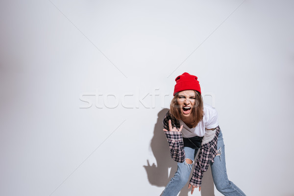 Woman dressed in shirt in cage print make rock gesture Stock photo © deandrobot