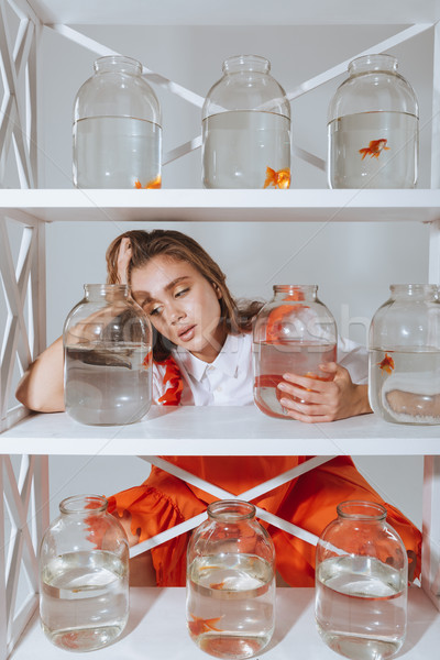Sad tired young woman leaning on shelf with gold fishes Stock photo © deandrobot