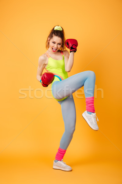 Amazing young sports woman boxer posing over yellow background Stock photo © deandrobot
