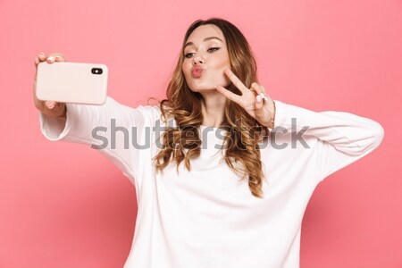 Woman sending kiss and making selfie with mobile phone Stock photo © deandrobot
